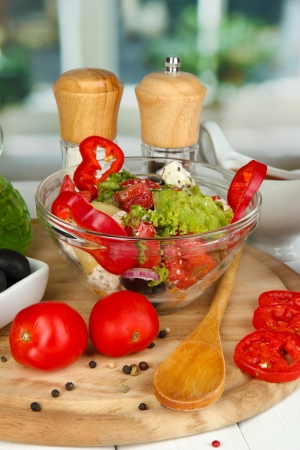 Fresh greek salad in glass bowl surrounded by ingredients for cooking on wooden table on window background close-up Stock Photo - 15897402