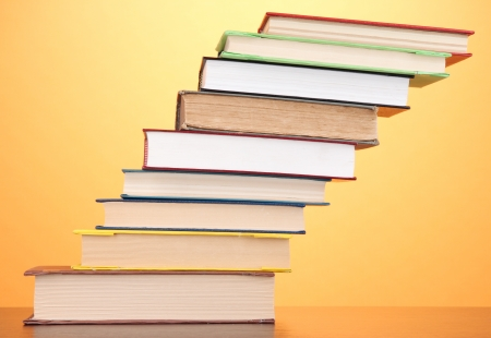 Stack of interesting books and magazines on wooden table on orange background photo