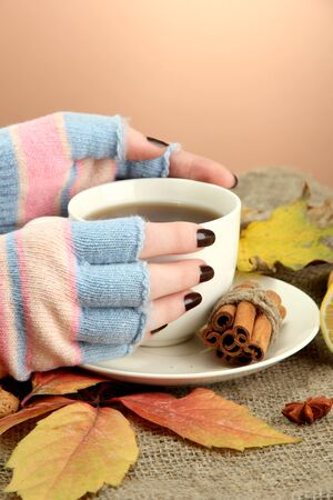 hands holding cup of hot drink and autumn leaves, on burlap background photo