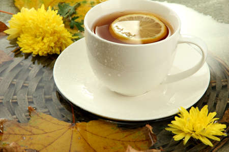 cup of hot drink and autumn leaves, close up photo