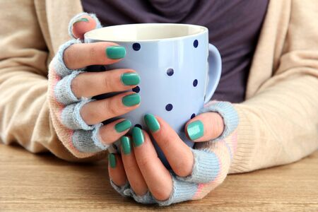 hands holding mug of hot drink, close-up photo
