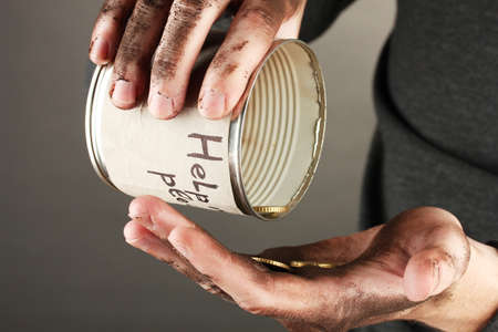 wastrel: homeless pours money from bank, close-up Stock Photo