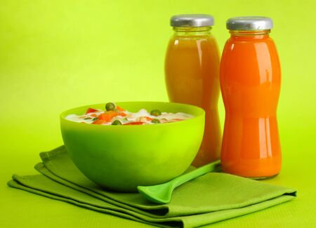 tasty  dieting food and bottles of juice, on green background photo