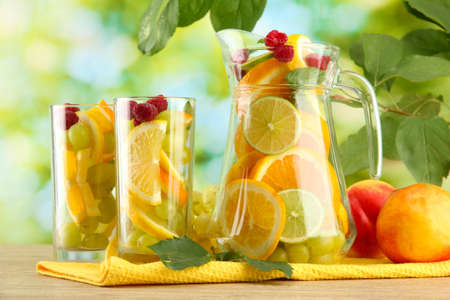 jar and glasses with citrus fruits and raspberries, on green background Stock Photo - 15923913
