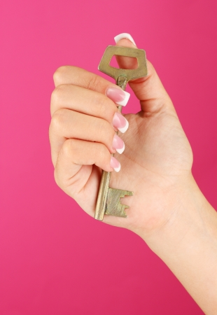Woman's hand with key, on pink background close-up photo