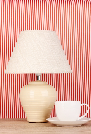 table lamp and cup on striped background photo