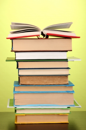 newspaper stack: Stack of interesting books and magazines on wooden table on green background Stock Photo