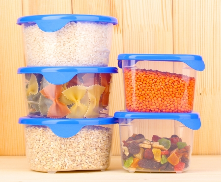 tupperware: Filled plastic containers on wooden background