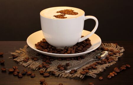Latte on wooden table on brown background photo