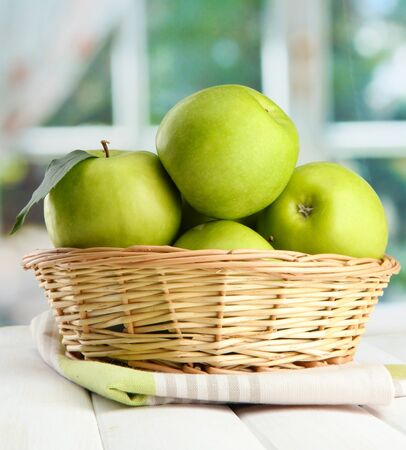 Ripe green apples with leaves in basket, on wooden table, on window background photo