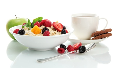 english breakfast: tasty oatmeal with berries and cup of tea, isolated on white