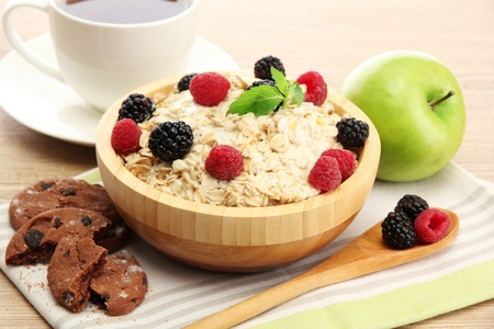 tasty oatmeal with berriesand cup of tea, on wooden table photo