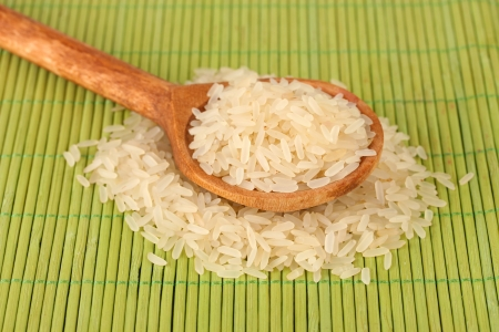 rice  in wooden  spoon on bamboo mat Stock Photo - 15943314