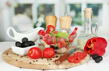 Fresh greek salad in glass bowl surrounded by ingredients for cooking on wooden table on window background Stock Photo - 15943284
