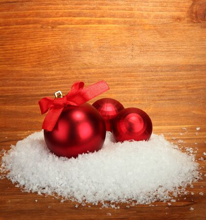 beautiful red Christmas balls on snow, on wooden background photo