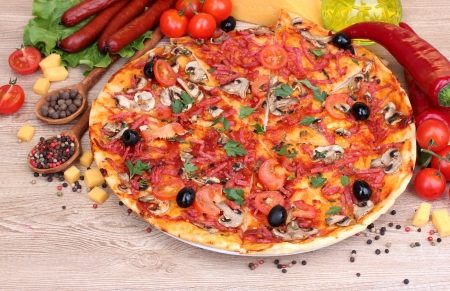 delicious pizza, vegetables and salami on wooden table photo