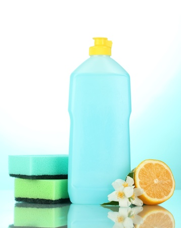 Dishwashing liquid with sponges and lemon with flowers on blue background photo