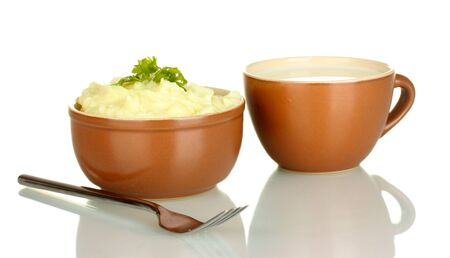 Mashed potato with parsley in the bowl and cup with milk isolated on white photo