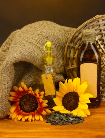 oil in bottles, sunflowers and seeds, on wooden table on brown background photo