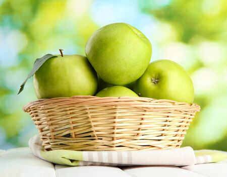 Ripe green apples with leaves in basket, on wooden table, on window background Stock Photo - 15958906