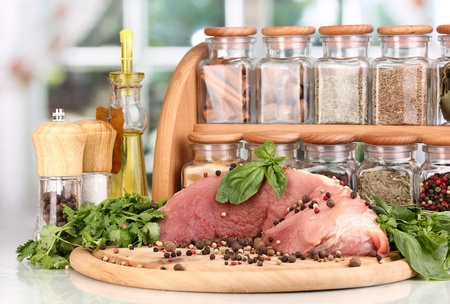 A large piece of pork marinated with herbs, spices and cooking oil on board on white table on window background Stock Photo - 15959712