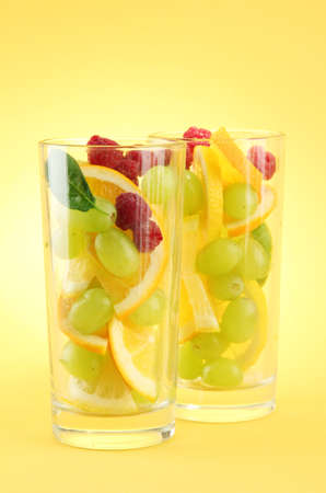 transparent glasses with citrus fruits, on yellow background Stock Photo - 15958710