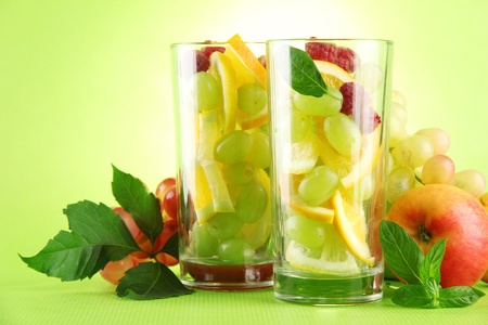 transparent glasses with citrus fruits, on grren background Stock Photo - 15958956