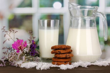 pasteurized: Pitcher and glass of milk with cookies on wooden table on window background Stock Photo