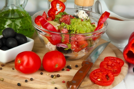 Fresh greek salad in glass bowl surrounded by ingredients for cooking on wooden table on window background close-up Stock Photo - 15959960