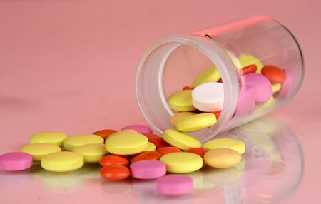 Pills in receptacle on red background photo