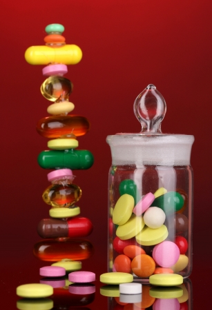 Capsules and pills hill and in receptacle on red background photo