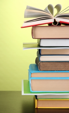 pile of books: Stack of interesting books and magazines on wooden table on green background Stock Photo