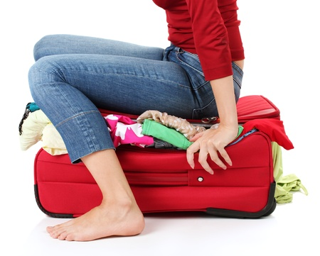 piece of luggage: The girl is trying to close suitcase crammed on white background Stock Photo