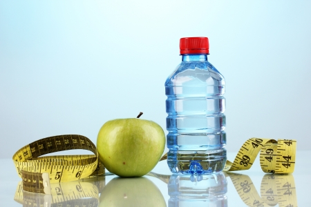 microelements: Bottle of water, apple and measuring tape on blue background