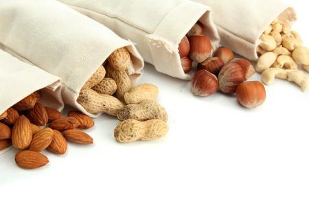 frutos secos: surtido de sabrosos frutos secos en bolsas, aislados en blanco Foto de archivo