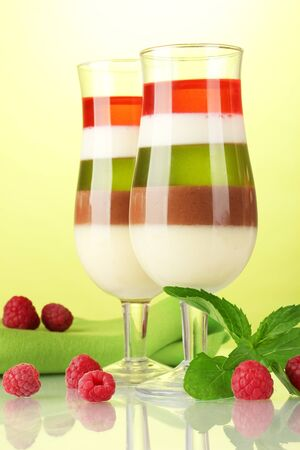 fruit jelly with berries in glasses on green background photo