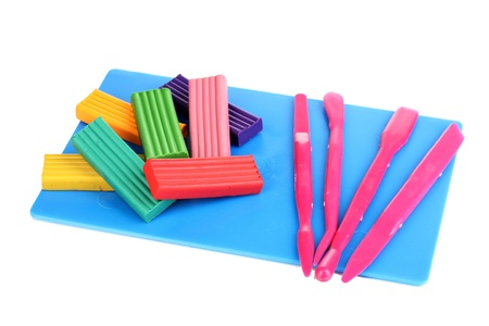 Children bright plasticine on desk with stacks isolated on white photo