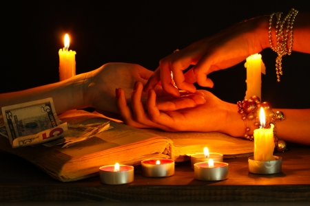 astrologer: reading the lines hand in a womans hands on black backcground Stock Photo