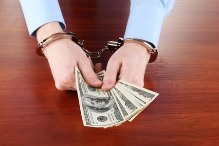 Businessman in handcuffs counts the money for bribes photo