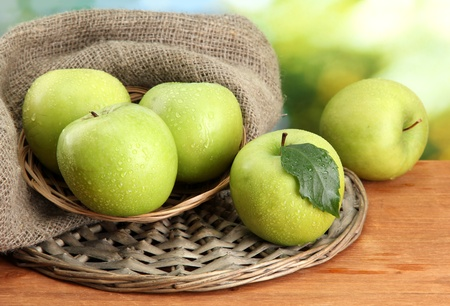 Ripe green apples in basket on burlap, on wooden table, on green background Stock Photo - 15994894