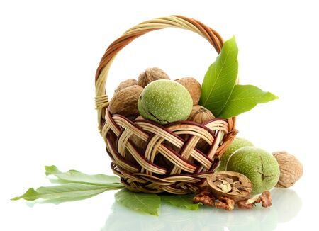 walnuts with green leaves in basket, isolated on white Stock Photo - 15994675