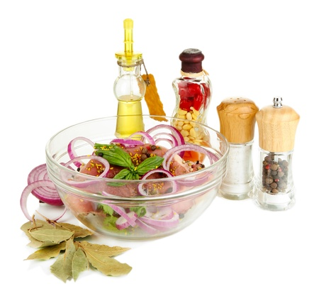 A large piece of pork marinated in bowl with herbs, spices and cooking oil isolated on white Stock Photo - 15994578