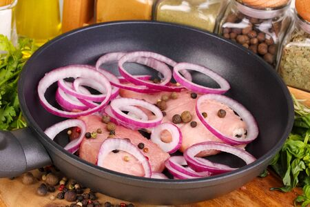 A pieces of pork with onions fried in pan with herbs, spices and cooking oil on board close-up Stock Photo - 15994907