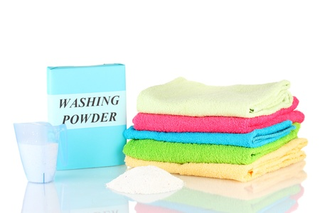 detergent: Box of washing powder with blue measuring cup and towels, isolated on white