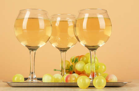 White wine in glass on salver on beige background photo