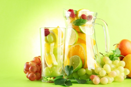 jar and glass with citrus fruits and raspberries, on green background Stock Photo - 15994700