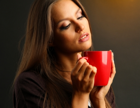 beautiful young woman with cup of coffee, on brown background photo
