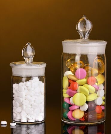 Capsules and pills in receptacles on orange background photo