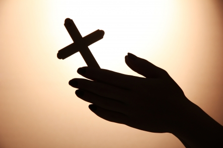 female hands with crucifix, on brown background photo