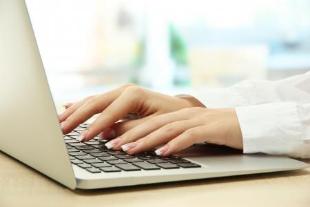 tabla de surf: manos femeninas que escriben sobre laptot, de cerca